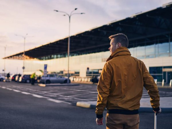 young-man-with-luggage-walking-to-airport-terminal-at-sunrise-prague-czech-republic_t20_VLRmR3